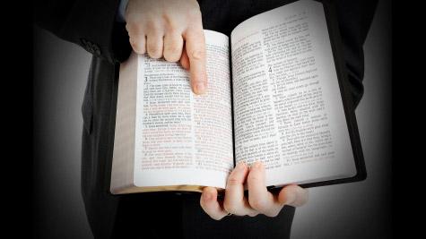 Biblia abierta y dedo apuntando