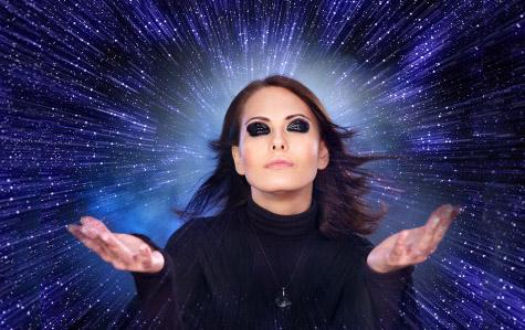 Mujer con vestimenta oscura con destellos de luz de fondo
